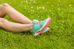 Woman in running shoes lying on grass Royalty Free Stock Photos