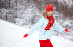 Woman running through snow. Young woman running through the snow, pulling a slay and smiling Royalty Free Stock Photos