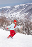 Woman running through snow. Young woman running through the snow, pulling a slay and smiling Royalty Free Stock Images
