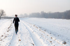 Woman running on the snow Royalty Free Stock Images