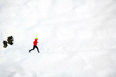 Woman running on snow in mountains Stock Photos
