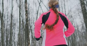 A young woman runs through the park in the winter in a pink jacket. View from the back stock video