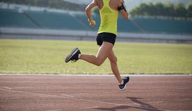 Woman running on stadium tracks stock photo