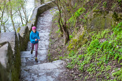 The woman running the stairs in the Park. The girl goes in for sports in the nature. Jogging in the spring woods Royalty Free Stock Image