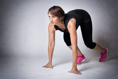 Woman in running start position Royalty Free Stock Photography