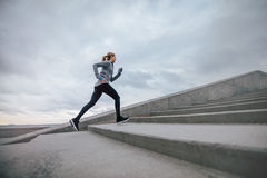 Woman running on steps outdoors royalty free stock images
