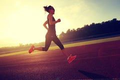 Woman running during sunny morning on stadium track Stock Photo