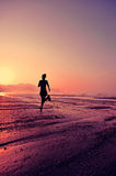 Woman running at sunrise beach Stock Image