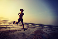 Woman running at sunrise beach Royalty Free Stock Photography