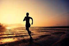 Woman running at sunrise beach Royalty Free Stock Photo