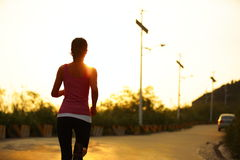 Woman running sunrise mountain road Royalty Free Stock Photography
