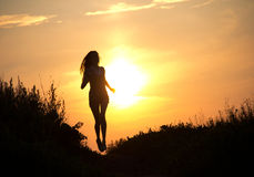 Woman running at sunset Stock Photography