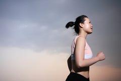 Woman running with sunset Stock Photos
