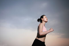 Woman running with sunset Stock Image