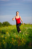 Woman running on a sunset field Royalty Free Stock Images