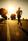 Woman running on sunset. Woman running marathon on beautiful golden summer sunset background in rural road. Female athlete fitness girl training and exercising Royalty Free Stock Images