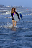 Woman running with surfboard Stock Images