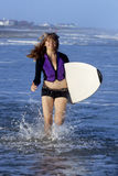 Woman running with surfboard Stock Image