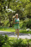 Woman running to keep fit. Woman running to keep & stay fit and healthy wearing green shorts and shirt Exercising outdoor royalty free stock images
