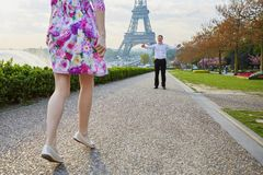 Woman running to man waiting for her with his arms open near Eiffel tower Royalty Free Stock Photo