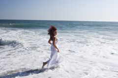 Woman running in to the waves Royalty Free Stock Photos