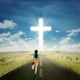 Woman running toward a cross Stock Photos
