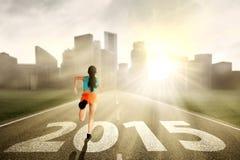 Woman running towards the future. Woman wearing fintess clothes, running towards the future 2015 Stock Photography