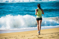 Woman running towards the sea Stock Photos