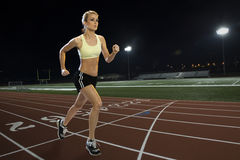 Woman running on a track Stock Photos