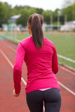 Woman running on track outdoors from back. Fitness, sport, training, people and lifestyle concept - african american woman running on track outdoors from back Stock Photography