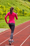 Woman running on track outdoors from back. Fitness, sport, training, people and lifestyle concept - african american woman running on track outdoors from back Royalty Free Stock Image