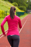 Woman running on track outdoors from back. Fitness, sport, training, people and lifestyle concept - african american woman running on track outdoors from back Stock Photos