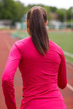 Woman running on track outdoors from back. Fitness, sport, training, people and lifestyle concept - african american woman running on track outdoors from back Stock Images