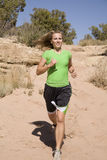 Woman running on trail. A woman wearing green running down a sandy trail in the outdoors Royalty Free Stock Images