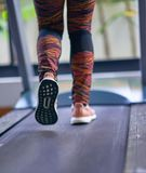 Woman running on treadmill in fitness gym with sport shoes ,back lower feet view,motion blur royalty free stock images