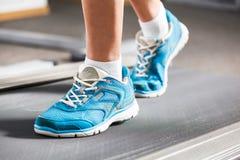 Woman running on treadmill. Royalty Free Stock Photos