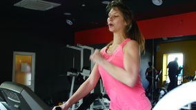 Woman running on treadmill in gym stock footage
