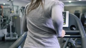 Woman running on treadmill in gym. Young woman running on treadmill in gym stock footage