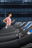 Woman running on treadmill in health club Stock Photography