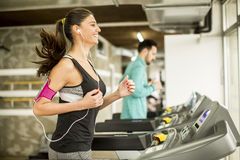 Woman running on the treadmill and listening to music at t. Young women running on the treadmill and listening to music at the gym Stock Image