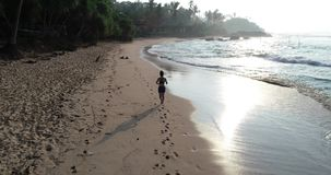 Woman running on tropical beach stock footage