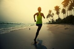 Woman running on tropical beach during sunrise royalty free stock images