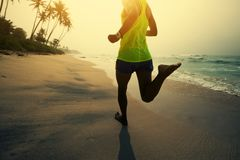 Woman running on tropical beach during sunrise royalty free stock photography