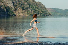 Woman running on tropical beach Stock Photography