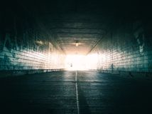 Woman running through tunnel towards bright light. Silhouette of woman running through dark urban tunnel Royalty Free Stock Images