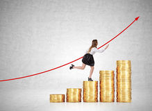 Woman running up coins stairs near concrete wall Royalty Free Stock Photography