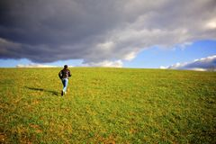 Woman Running Up Hill. With dark clouds Stock Photo