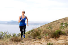 Woman running up hill with sea in background. Full length portrait of woman running up hill with sea in background Royalty Free Stock Images