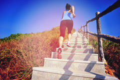 Woman running up on mountain stairs Stock Photo