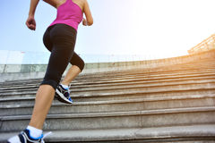 Woman running up on mountain stairs Stock Image